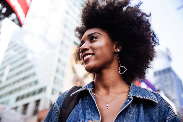 Low Angle View Of Happy Young Woman With Afro Hairstyle In City