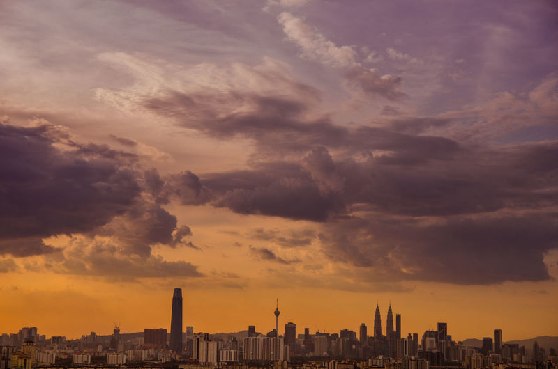 Buildings in city against cloudy sky during sunset