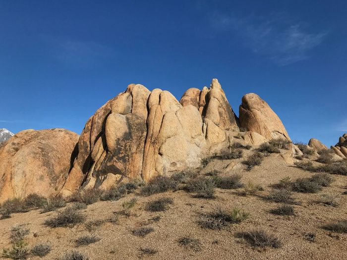 Low angle view of vertical rock formations in the desert Alabama Hills, CA Boulder Sky Nature Blue Beauty In Nature Tranquility Scenics - Nature Tranquil Scene Solid Sunlight Non-urban Scene Rock - Object Desert No People Day Low Angle View Remote Rock Formation Arid Climate Rock Land