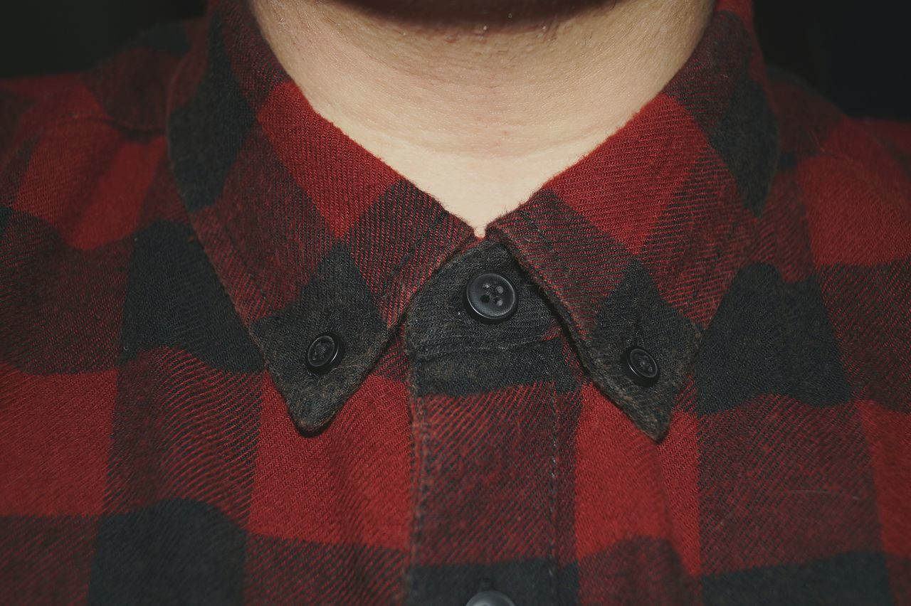Midsection of man wearing checked shirt