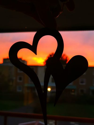 Close-up of silhouette heart shape against orange sky