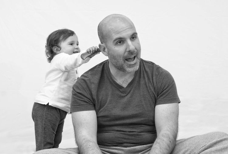 Cute girl combing hair of father while sitting against wall at home