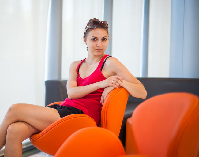 Adult Beautiful Woman Casual Clothing Chair Front View Indoors  Leisure Activity Lifestyles Looking At Camera One Person Orange Color Portrait Real People Seat Sitting Three Quarter Length Women Young Adult Young Women