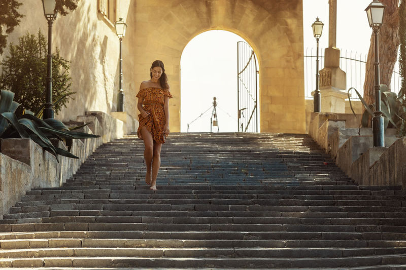 Low angle view of woman walking on staircase of building