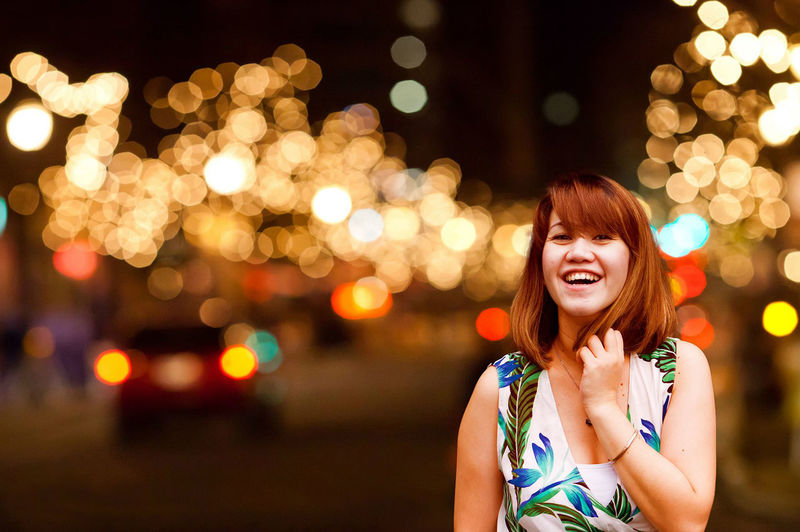 Portrait Of Happy Woman In City Against Illuminated Street Light