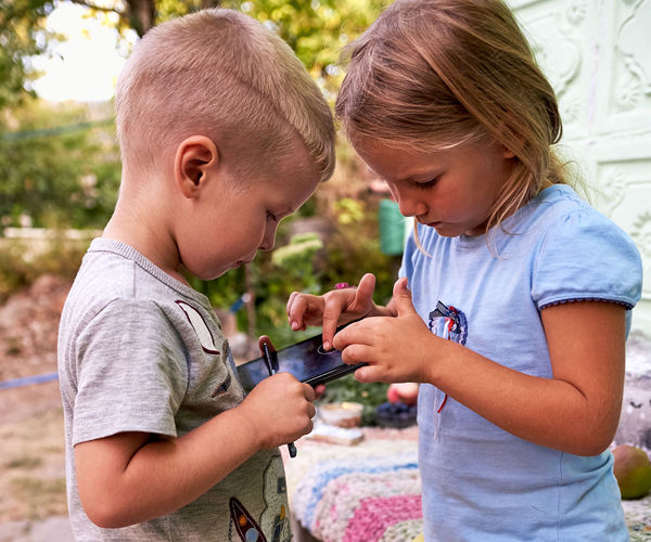 Side view of siblings using smart phone