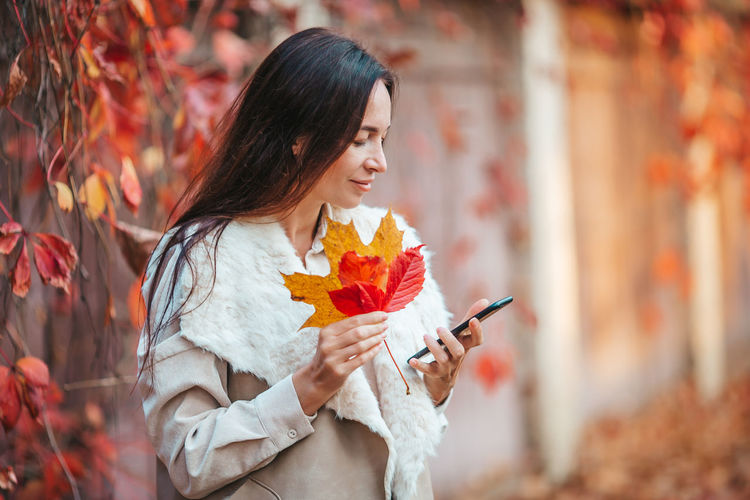 Young woman holding autumn leaf outdoors