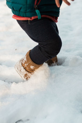 Boots in the snow Winter Boot Child Childhood Clothing Cold Cold Temperature Cute Day Deep Human Body Part Human Leg Kid Leisure Activity Lifestyles Low Section Motion Nature One Person Outdoors People Real People Snow Toddler  White