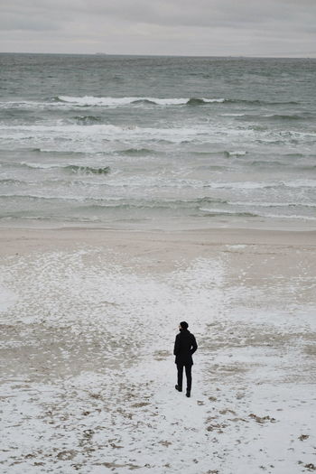 Rear view of men at beach against sky