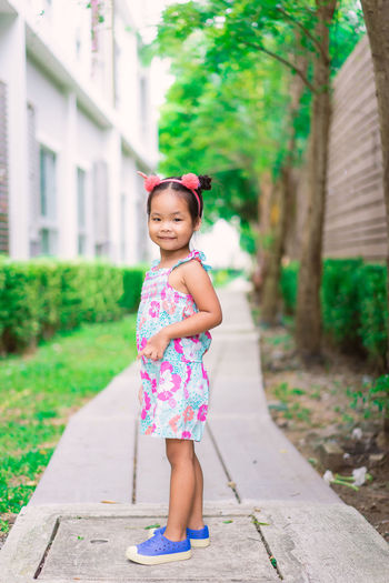 Full length portrait of cute girl standing on footpath