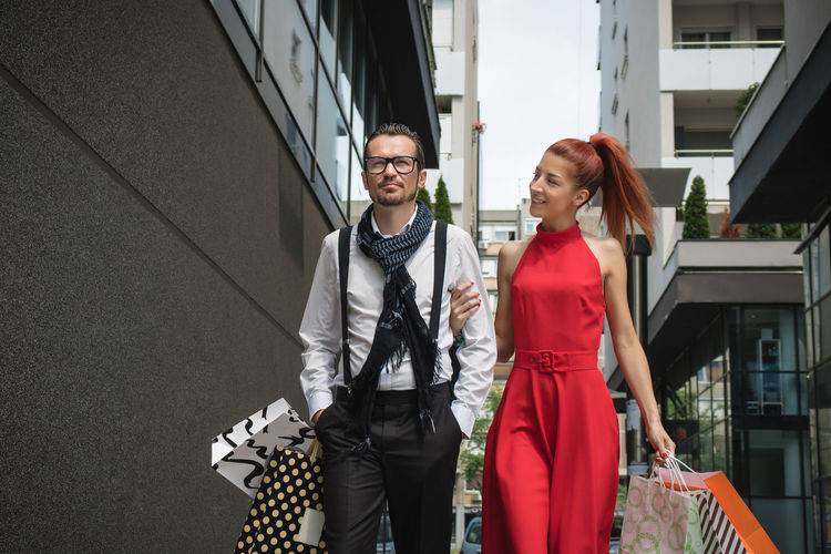 Couple holding shopping bags while walking amidst buildings in city