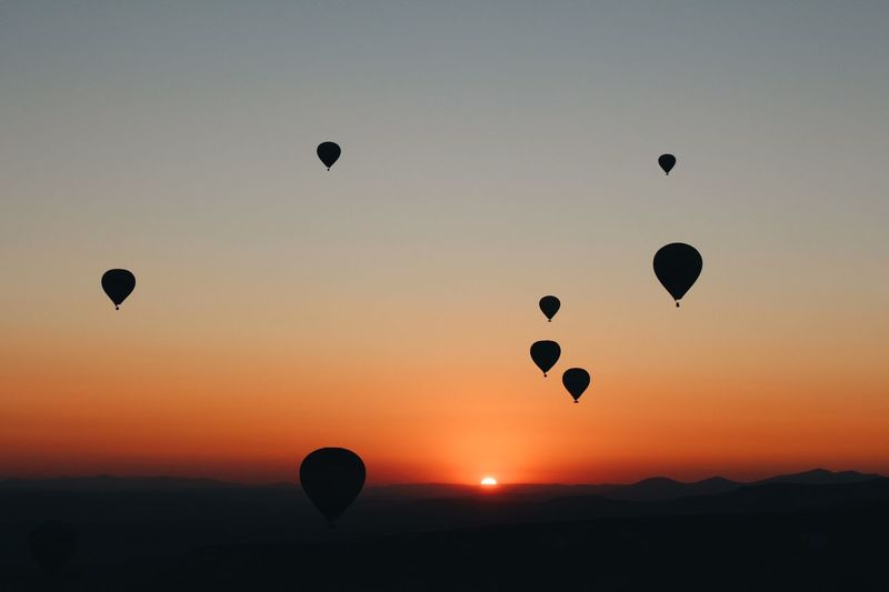 Silhouette hot air balloons flying in sky during sunset