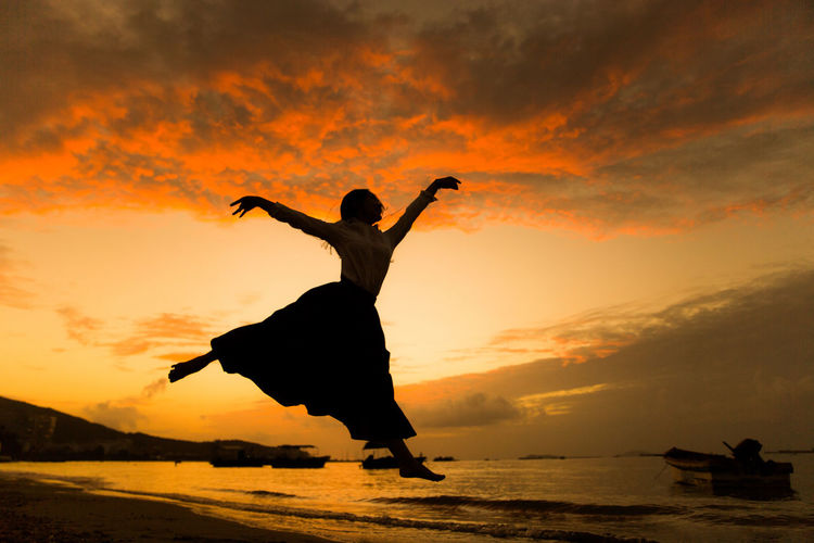 Silhouette of woman jumping in sea at sunset