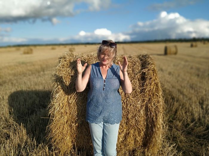 Midsection of woman with hay bales on field against sky