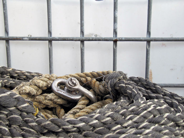 Close-Up Of Ropes With Hook By Railing Against Wall