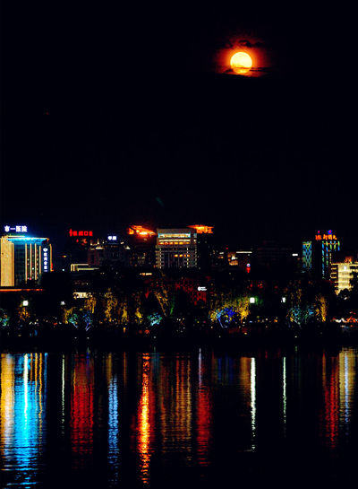 Illuminated buildings by river against sky at night