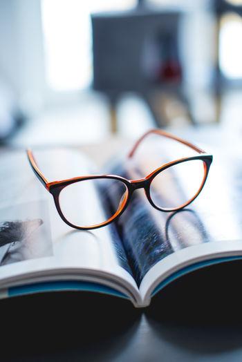 Close-Up Of Eyeglasses On Magazine