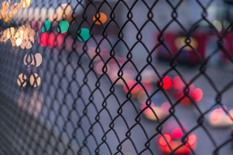 Full frame shot of chainlink fence in illuminated city during dusk