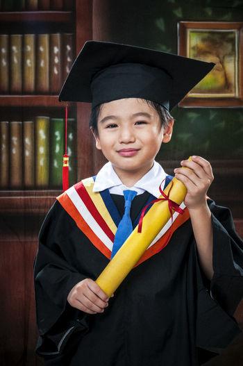 Portrait of happy boy wearing graduation gown