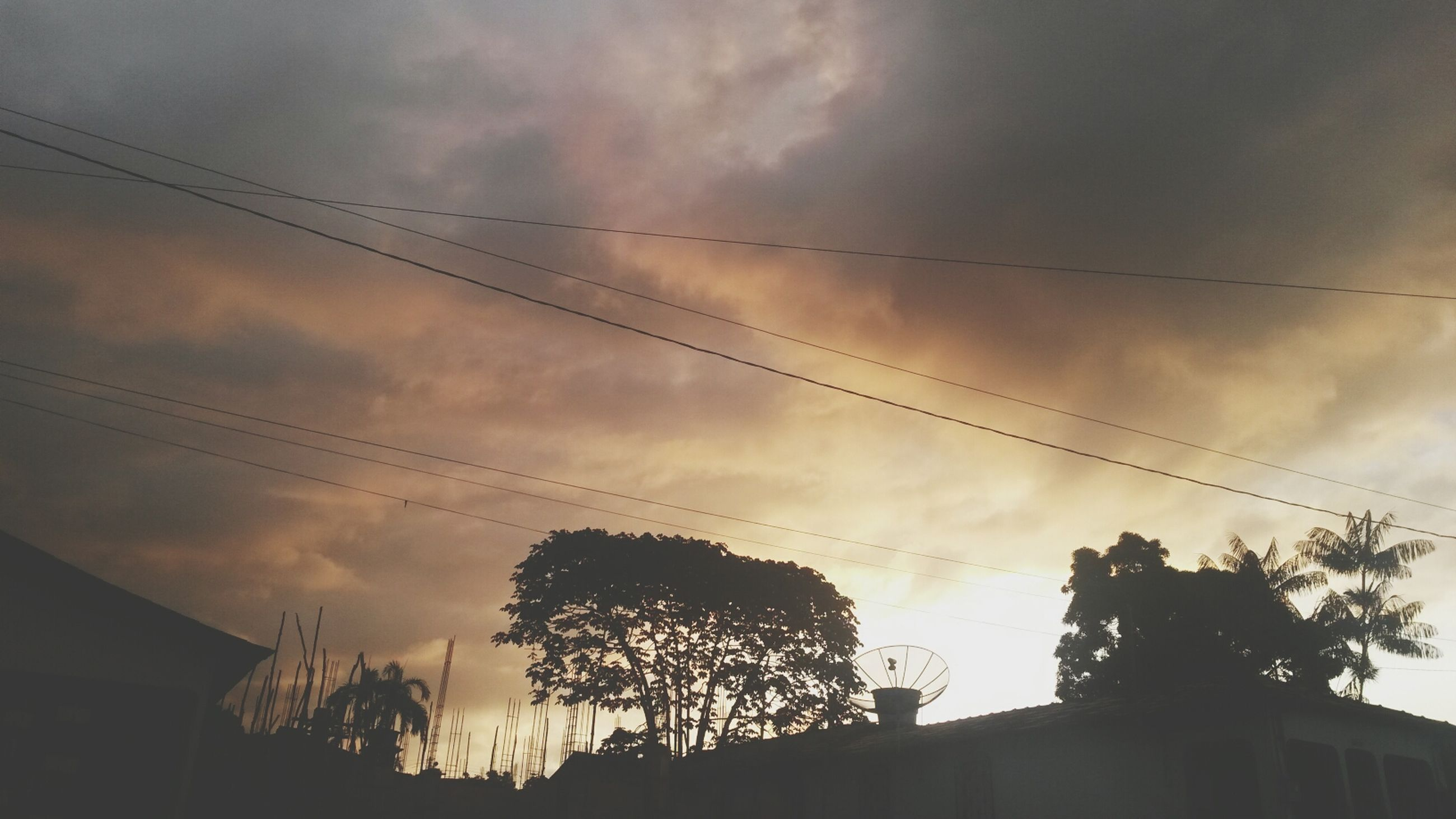 power line, low angle view, sky, silhouette, cloud - sky, cable, electricity pylon, tree, power supply, cloudy, electricity, built structure, architecture, building exterior, connection, cloud, power cable, house, sunset, dusk