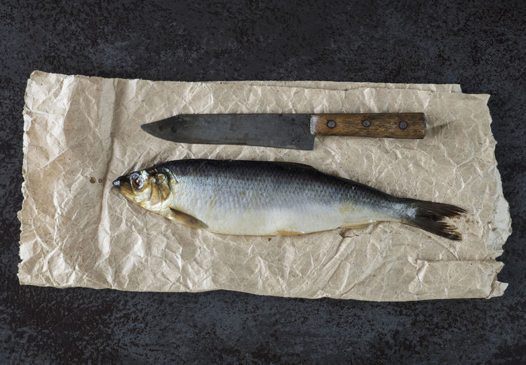 Directly above shot of salted herring on crumpled paper at black table