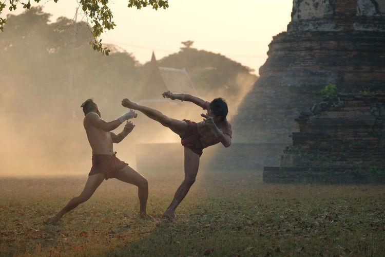 Full length of shirtless men boxing on land against sky