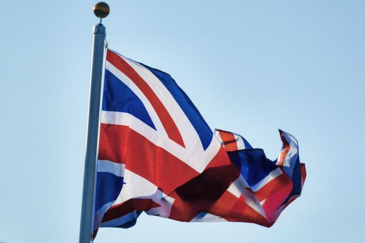 Low angle view of british flag waving against clear sky