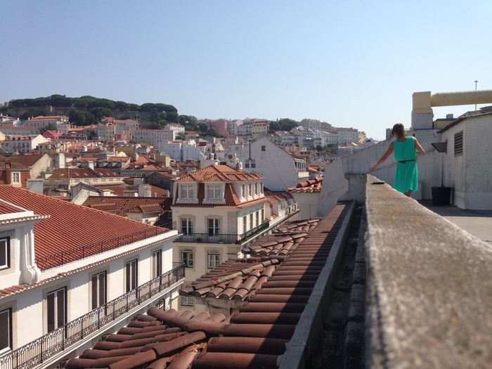 Rear View Of Woman Walking On Building Terrace In Town Against Clear Sky