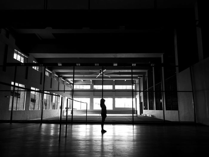Silhouette Of Woman Standing At Tennis Court