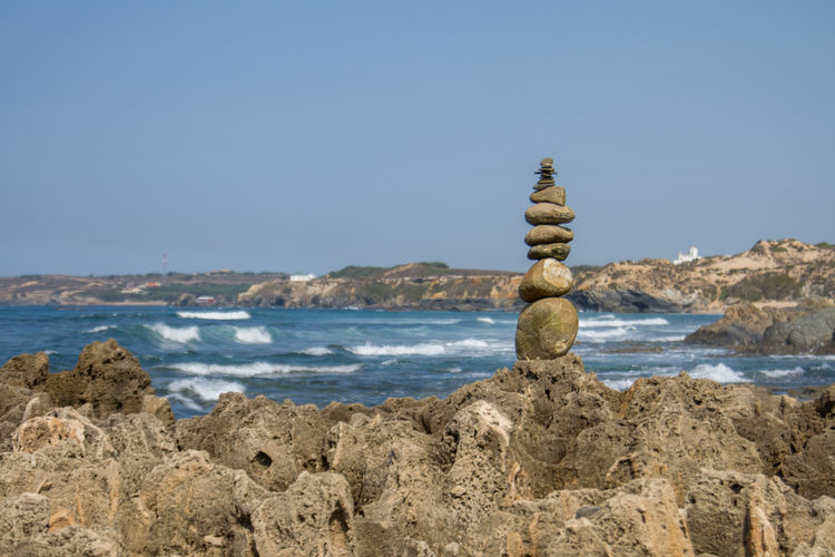 Statue on rock by sea against clear sky