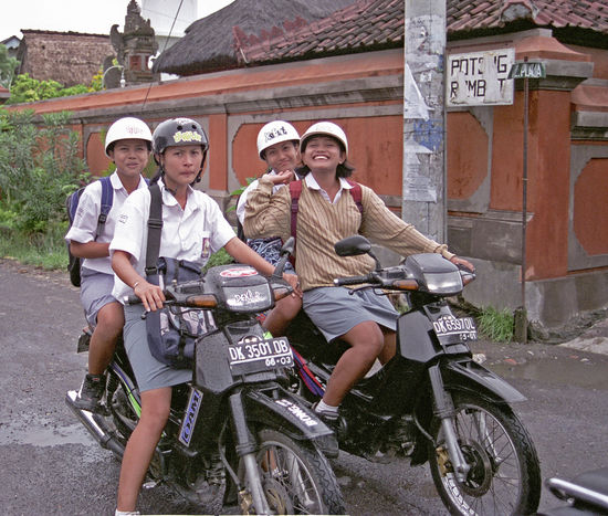 Bali, Indonesia Building Exterior Delight  Expressions Girls Happiness Hat Helmet Looking At Camera Moped School Sidestreet Sitting Smiling Suspicion Traffic Transportation Travel Uniform Women Young Women