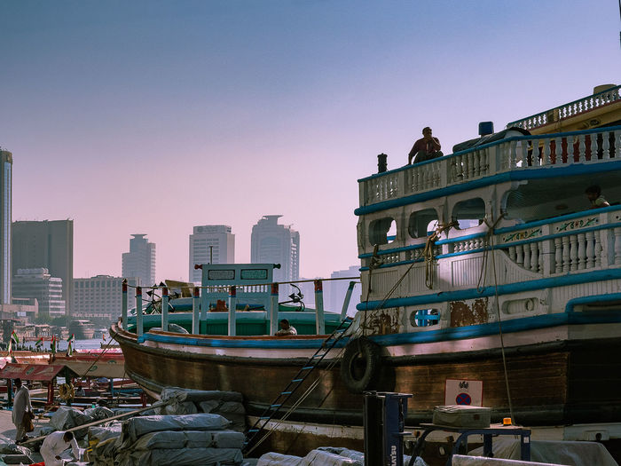 Boats moored at harbor by buildings against sky during sunset