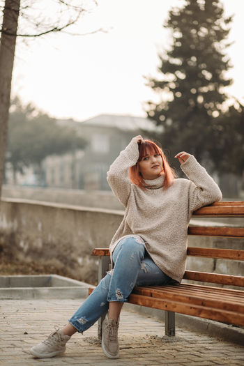 One Person Full Length Sitting Casual Clothing Young Adult Leisure Activity Real People Lifestyles Adult Relaxation Winter Women Young Women Clothing Bench Day Seat Warm Clothing Beautiful Woman Jeans Outdoors Contemplation