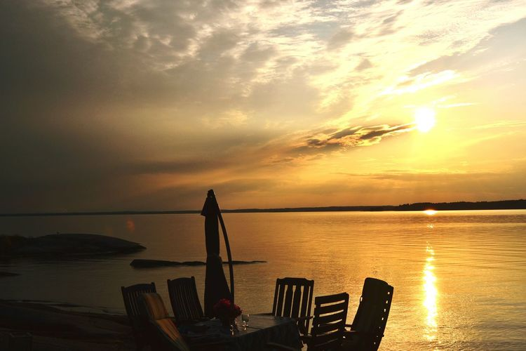 Table and chairs arranged at sea shore during sunset