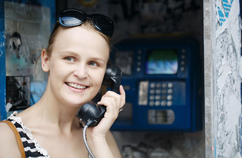 Happy young woman talking on pay phone