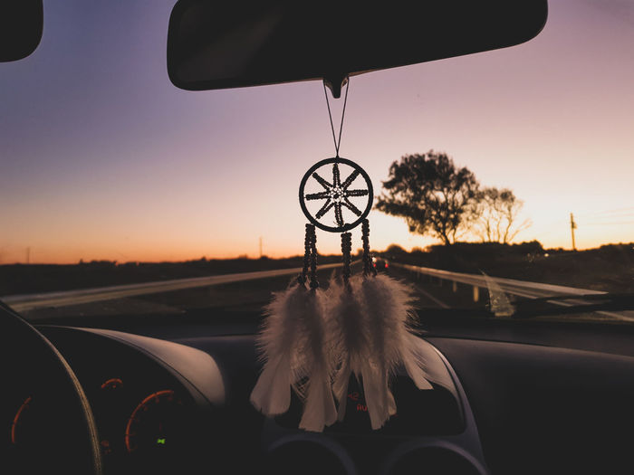 Close-Up Of Dreamcatcher Hanging On Rear-View Mirror Of Car During Sunset