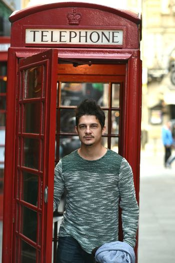 Young man standing at telephone booth in city
