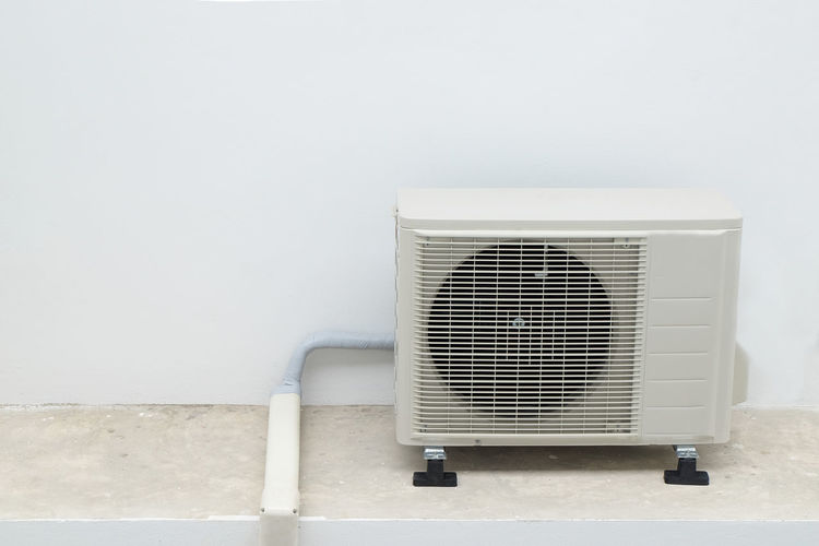 Close-up of air conditioner against white wall
