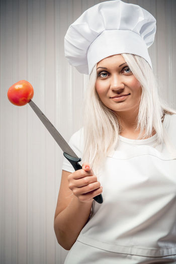 Woman cook indoors, weight loss concept Apron Cook  Cooking Culinary Diet Eating Uniform Vegetarian Food Weight Loss Woman Blond Hair Caucasian Chef Hat Concept Conceptual Dieting Healthy Eating Healthy Food One Person Tomato Vegetable Vegetables