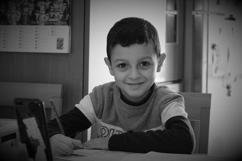 Portrait of smiling boy sitting at home