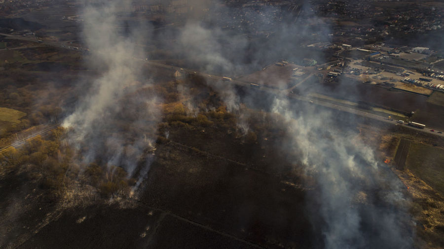 Massive fire, dry grass lanes in fire, firefighters at work, disaster, ecological catastrophe