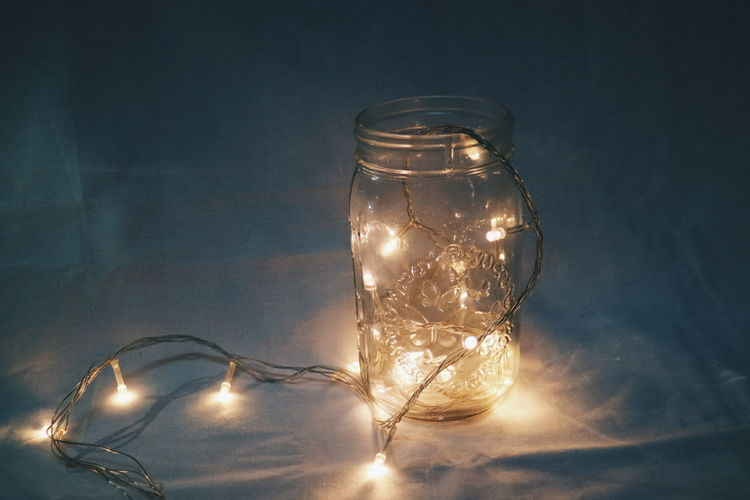Close-up of illuminated lights in jar on table