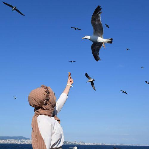 Young woman feeding birds against sky