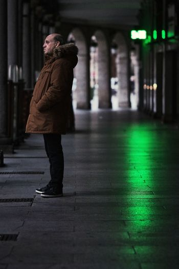 Side view of man standing on footpath at night