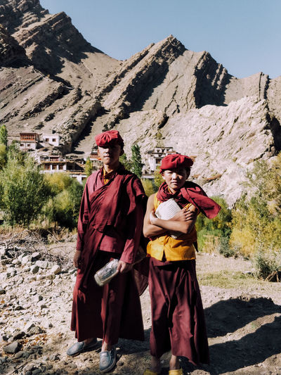 Portrait of two young novice monks in traditional red robes standing on a mountain in Leh Ladakh, India. Younger boys often opt for monk hood as it is their culture. Buddhism flows through Ladakh. Mountain Nature Real People Sunlight Togetherness Clothing Traditional Clothing Mountain Range Lifestyles Outdoors Novice Monk Tibetan  Tibetan Buddhism Tibetan Culture Buddhism Buddhist Monks Children Childhood Sunlight And Shadow Portrait Photography Portrait Of A Man  Full Length Worship Belief Culture And Tradition