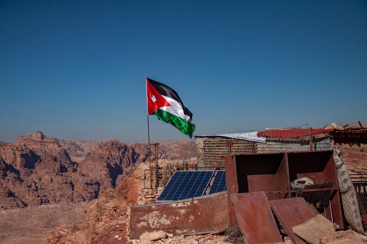 Flag by building against clear blue sky