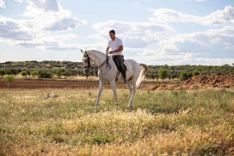 Full length of a young man riding horse on field