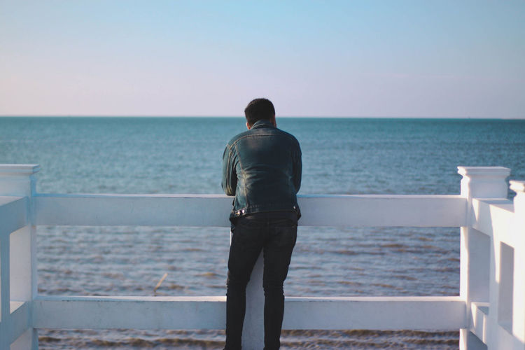 Rear view of young man looking at sea while standing by railing against clear sky