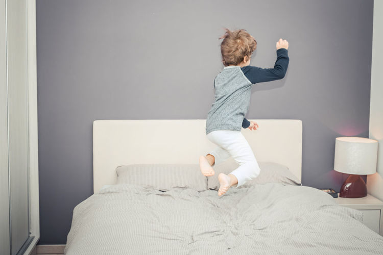 Rear view of boy jumping on bed at home