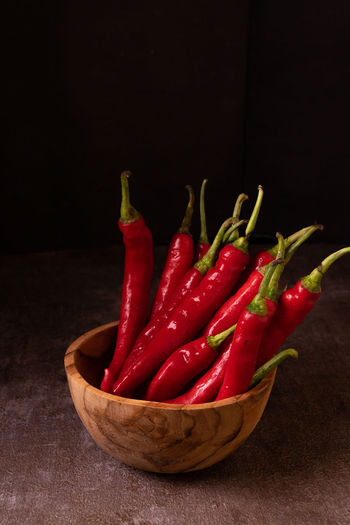 Close-up of red chili peppers on table against black background